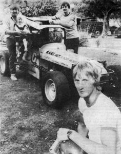 THE CHALLENGERS: Phil Blake, foreground, Rod Blatchford nursing Blake's daughter Tennille, 2; and Noel Sharrock. The car is the one Blake will use on Sunday. PHOTO: Wimmera Mail-Times