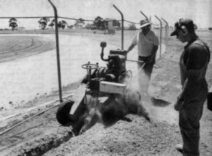 HARD AT WORK: Horsham Motor Sports Club member Chris Wilde, left, operates a Ditch Witch to dig a trench for electrical cable which will power the track's race lights. Simon Smith of Kalkee is also pictured. Wilde spent 13 hours on the machine. A fence in the background is now finished. Trevor and Helen Simmons spent two days painting the white concrete track wall also pictured in the background. PHOTO: The Wimmera Mail-TImes
